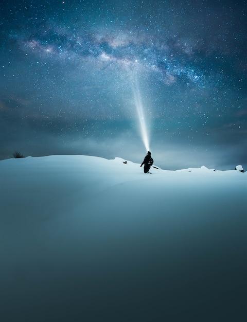 Concetto di fantasia di un viaggiatore che brilla e illumina il bellissimo cielo stellato con la torcia Foto Gratuite