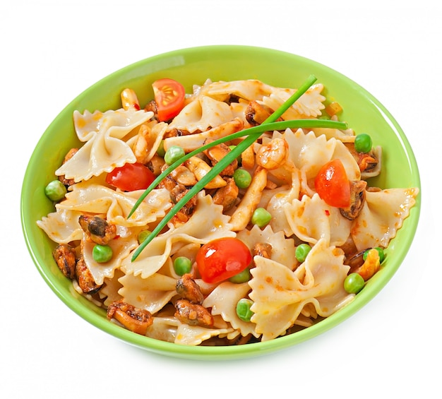 Farfalle pasta with seafood, cherry tomatoes and green peas Free Photo