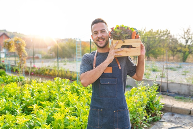 Farmer holding in his hands wooden box with local vegitables. Premium Photo