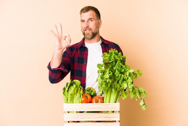Farmer senior man on beige wall cheerful and confident showing ok gesture. Premium Photo