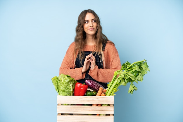 Farmer with freshly picked vegetables in a box scheming something Premium Photo