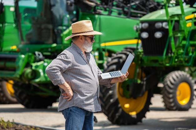 Un contadino con trattati e laptop Foto Gratuite