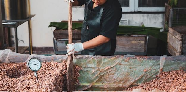 農家はカカオ豆を発酵させてチョコレートを作っています。 Premium写真