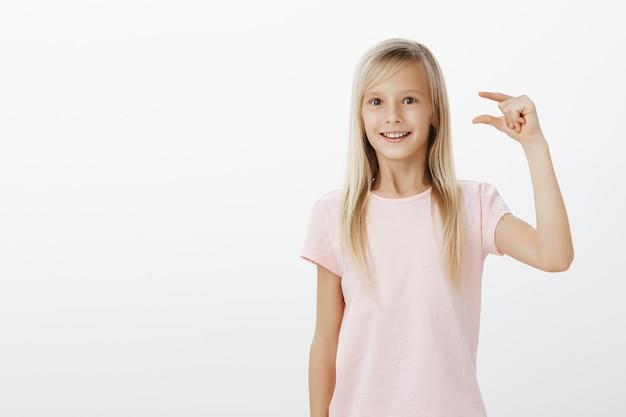 Affascinata bambina sognante con i capelli biondi in maglietta rosa, che plasma qualcosa di piccolo o minuscolo con le dita, stupita dall'uccellino che ha visto nel parco, in piedi sorpresa sul muro grigio Foto Gratuite
