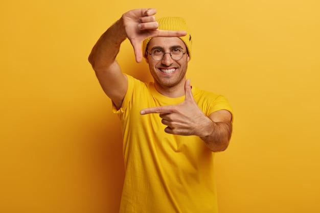 Очарованный молодой человек с веселым выражением лица делает рамку от руки, пытается найти правильную перспективу, изображает сцену съемки Бесплатные Фотографии