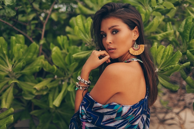 Fascinating asian woman with tan skin posing over green palm trees Free Photo