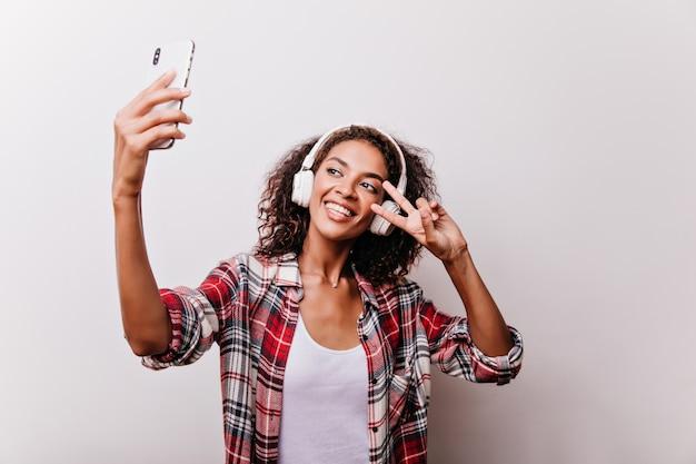 Очаровательная черноволосая девушка позирует со знаком мира для селфи. привлекательная молодая женщина в белых наушниках, держа смартфон. Бесплатные Фотографии