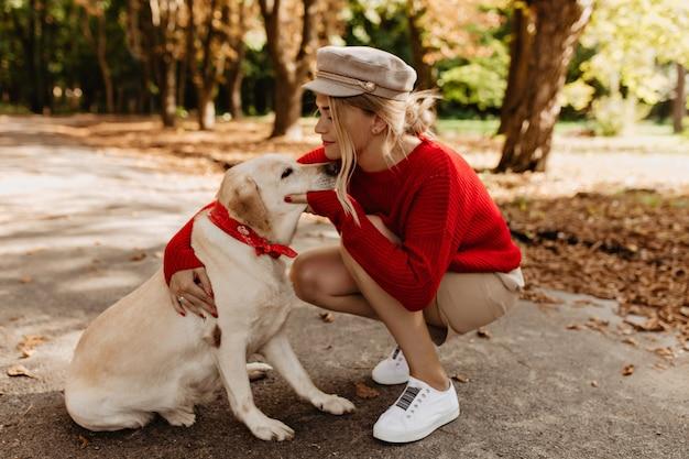 가을 공원에서 함께 하루를 보내는 사랑스러운 래브라도와 매혹적인 금발. 그녀의 사랑하는 개를 껴안고 계절 옷을 입은 소녀의 감동적인 사진. 무료 사진