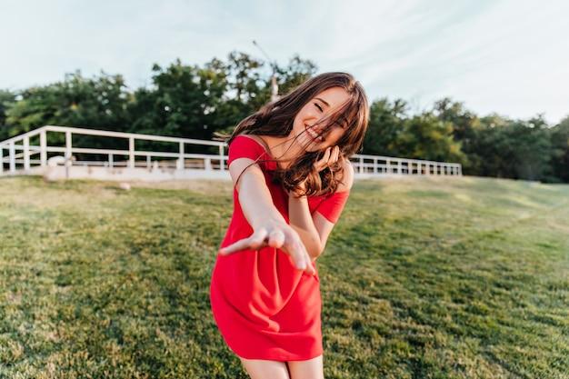夏の日の屋外写真撮影を楽しんでいる魅力的な茶色の髪の女性。緑の芝生の上に立っている赤いドレスを着たうれしそうな笑いの女性モデル。 無料写真