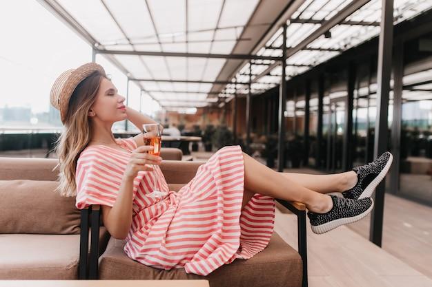 와인 글라스와 함께 카페에서 포즈 검은 운동화에 매혹적인 백인 소녀. 레스토랑에서 재미 모자에 사랑스러운 금발 여성 모델의 초상화. 무료 사진