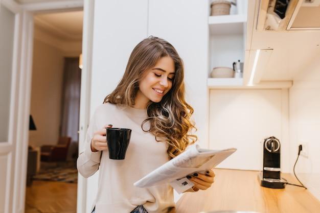 彼女の台所で薄茶色の髪の読書ジャーナルを持つ魅力的な女性モデル 無料写真