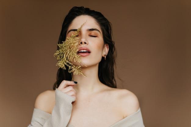 녹색 잎을 들고 눈을 감고 서있는 매혹적인 소녀. 실내 촬영을 즐기는 유행 편안한 여자. 무료 사진