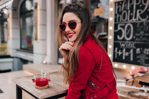 Очаровательная девушка в солнцезащитных очках в форме сердца, глядя через плечо, сидя за деревянным столом Бесплатные Фотографии