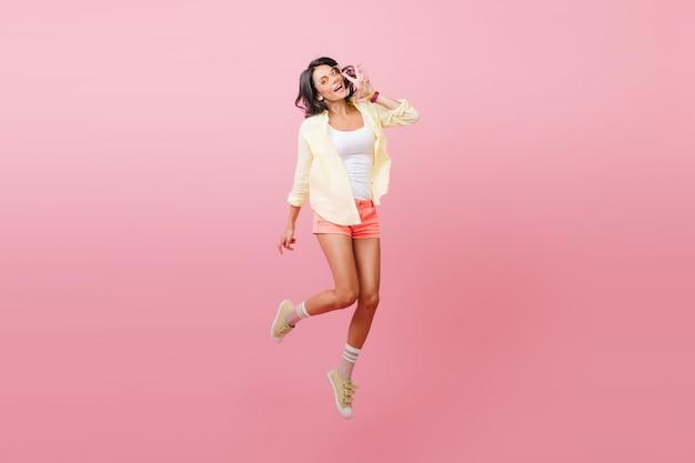 Affascinante ragazza hipster in abito giallo trascorrere del tempo. romantica signora ispanica in scarpe da ginnastica alla moda ballando con piacere. Foto Gratuite