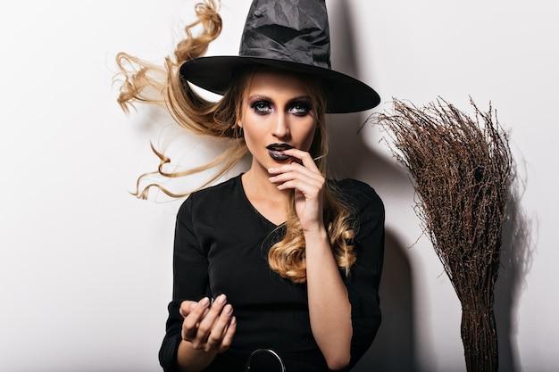 Очаровательная женщина с черным макияжем, наслаждаясь карнавалом. фото модной блондинки в костюме хеллоуина. Бесплатные Фотографии