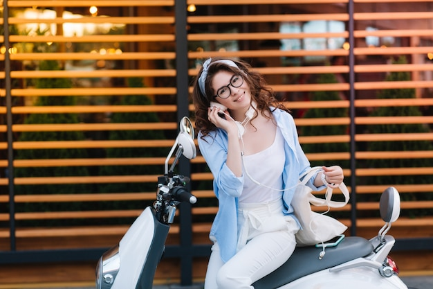 Fascinating young lady in stylish glasses holding white eco bag and listening music in earphones, resting after shopping Free Photo