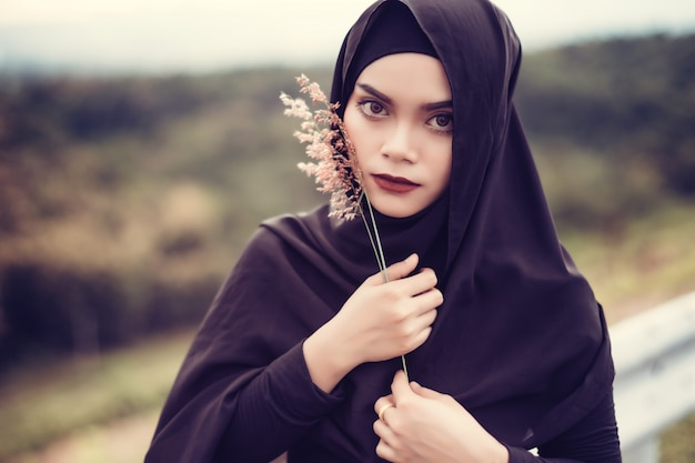 Fashi portrait of young beautiful muslim woman with the black hijab.muslim woman holding grass flower.vintage style Premium Photo