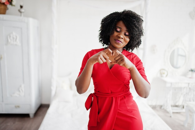 Fashion african american model in red beauty dress, sexy woman posing evening gown in white vintage room and show heart by hands. Premium Photo