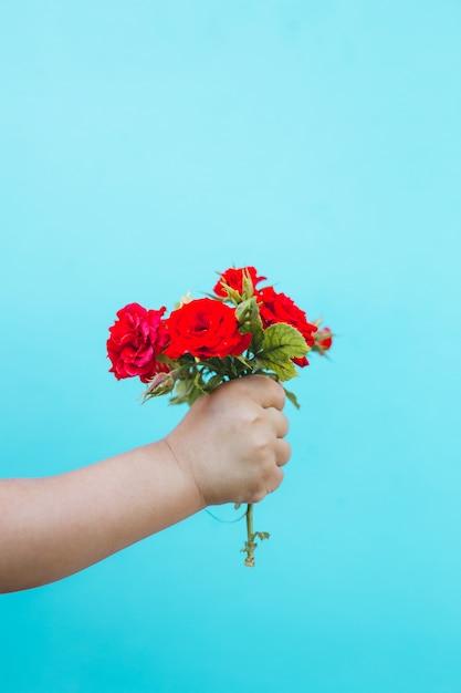 Fashion art hand of a little child holding rose  bouquet Premium Photo