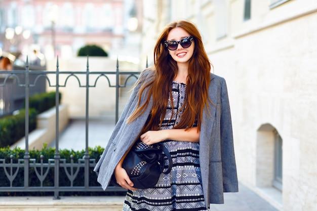 Осенний модный портрет стильной рыжей женщины, позирующей на улице, женственный нежный элегантный повседневный наряд, винтажные солнцезащитные очки, длинные волосы, уличный стиль. Бесплатные Фотографии