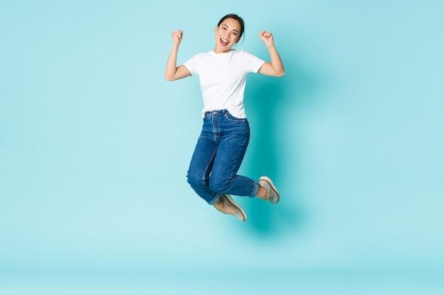 패션, 뷰티 및 라이프 스타일 개념. 쾌활한 승리, 행복과 기쁨에서 점프하는 매력적인 아시아 소녀, 경쟁에서 승리하고 밝은 파란색 벽에서 승리를 축하합니다. 무료 사진