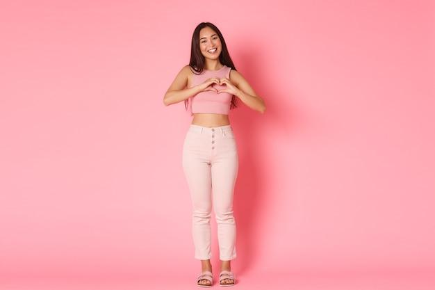 Концепция моды, красоты и образа жизни. полная длина милая, кокетливая азиатская девушка в гламурной одежде, демонстрирующая жест сердца, выражающая любовь, сочувствие и заботу, стоящая розовая стена. Premium Фотографии