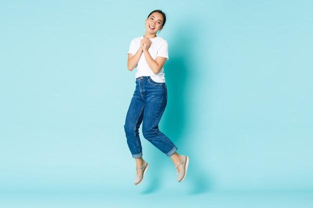 패션, 뷰티 및 라이프 스타일 개념. 행복과 꿈꾸는, 흥분된 아시아 소녀 캐주얼 복장, 행복과 기쁨에서 점프, 열정적 인 박수 손, 밝은 파란색 벽 위에 서서 무료 사진