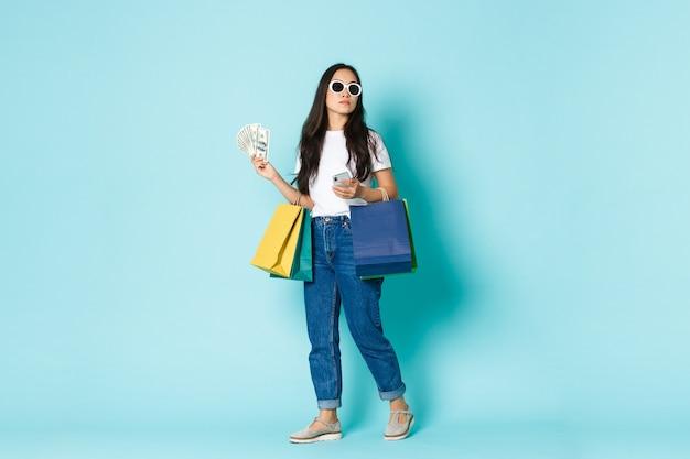 ファッション、美容、ライフスタイルのコンセプト。サングラスをかけた生意気な若いアジア人女性が買い物をしながら周りを見回し、お金を持って、服と携帯電話のバッグ、水色の背景。 Premium写真