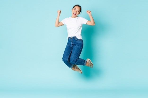 Fashion, beauty and lifestyle concept. cheerful triumphing, attractive asian girl jumping from happiness and joy, winning competition, celebrating victory over light blue wall Free Photo