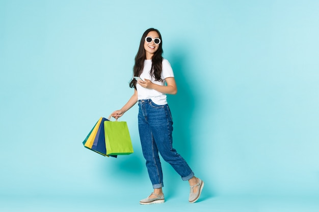 Fashion, beauty and lifestyle concept. dreamy attractive asian woman, walking along light blue wall with shopping bags and smartphone, wearing sunglasses Free Photo