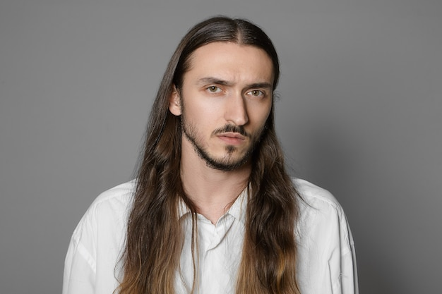 Fashion, beauty and style concept. head and shoulders of serious bearded man with pale skin and hairy face wearing his long brown hair loose Free Photo