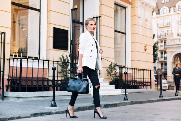 Fashion blonde woman on heels in white jacket  is walking on street. she is smiling to side. Free Photo