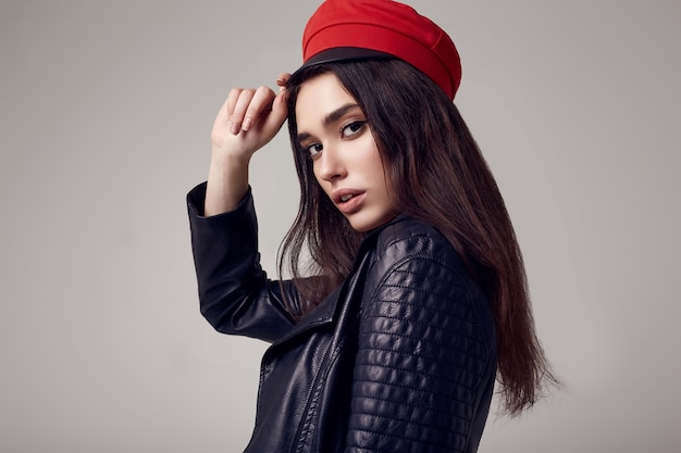 Fashion brunette woman wearing a leather jacket and red hat Premium Photo