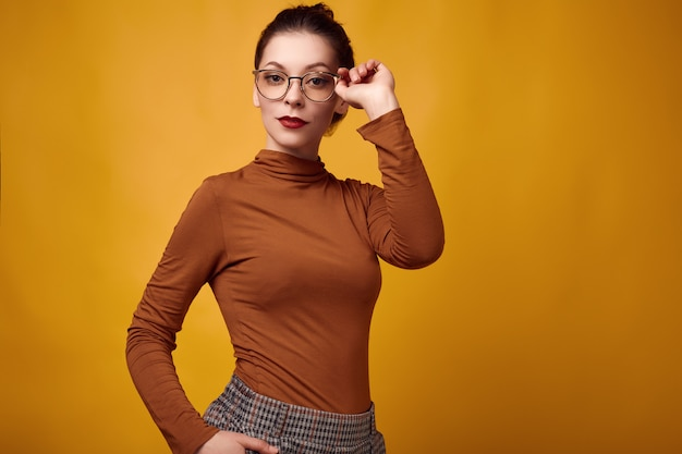 Fashion brunette woman wearing turtleneck and glasses on yellow background Premium Photo
