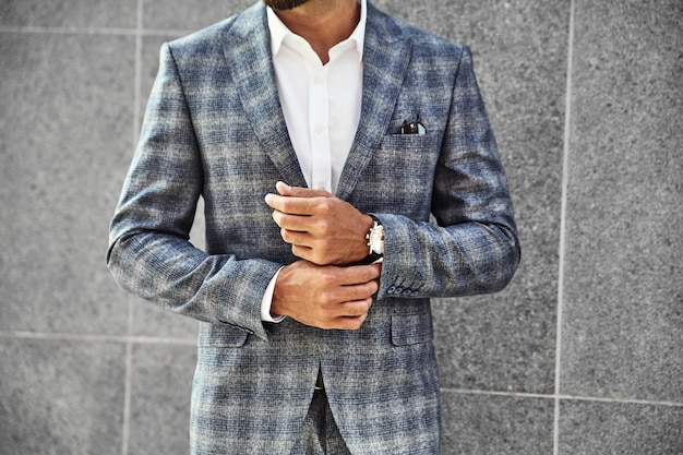 Fashion businessman model dressed in elegant checkered suit posing near gray wall on street background. metrosexual with luxury watch on wrist Free Photo