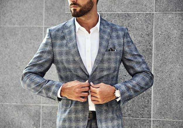 通りの背景に灰色の壁に近いポーズエレガントな市松模様のスーツに身を包んだファッション実業家モデル。手首に高級時計とメトロセクシャル 無料写真