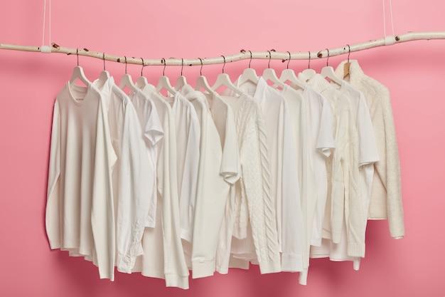 Модная одежда белого цвета, вязаные узоры, вешается на вешалки для демонстрации. ряд солидных нарядов в гардеробе. Бесплатные Фотографии