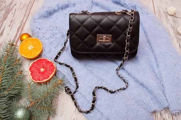 Fashion concept. black female bag on sweater, spruce branch and orange Premium Photo