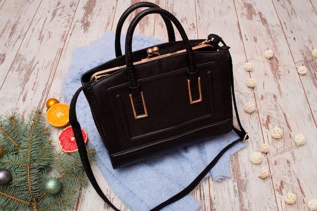 Fashion concept. black female bag, warm sweater, spruce branch and orange Premium Photo
