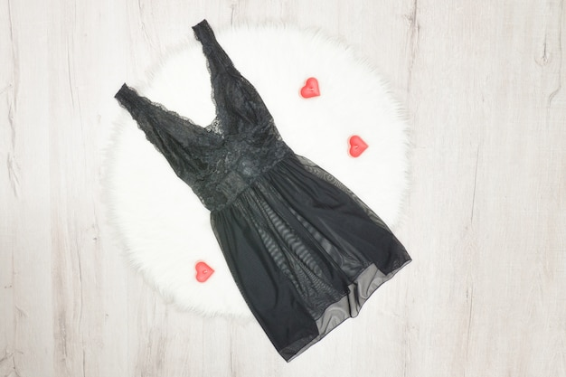 Fashion concept. black lacy nightie on white fur. red heartshaped candles Premium Photo