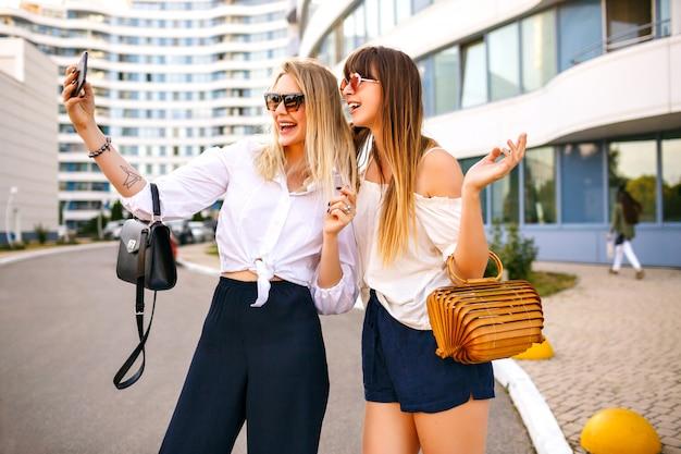 Модная пара красивой модной элегантной женщины, одетой в летний цвет, сочетающейся с классическими женственными нарядами, сумками и солнцезащитными очками, заставляет селфи наслаждаться временем вместе, путешествуя настроением, летом. Бесплатные Фотографии