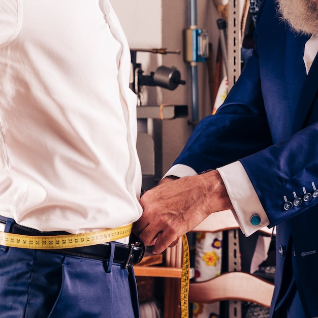 Fashion designer's hand taking measurement of his customer's waist with yellow measuring tape Free Photo