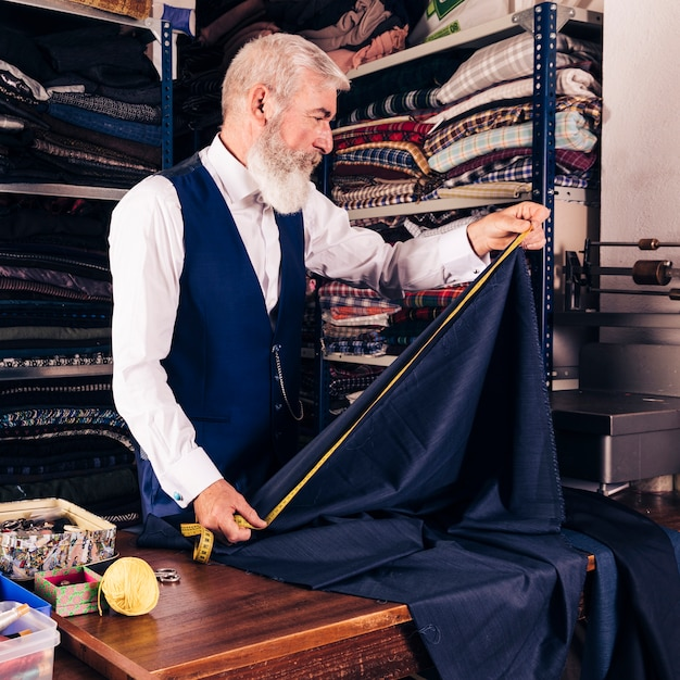 Fashion designer taking measurement of blue fabric with measuring tape on table Free Photo