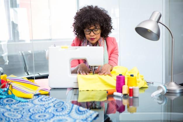 Fashion designer using sewing machine Premium Photo