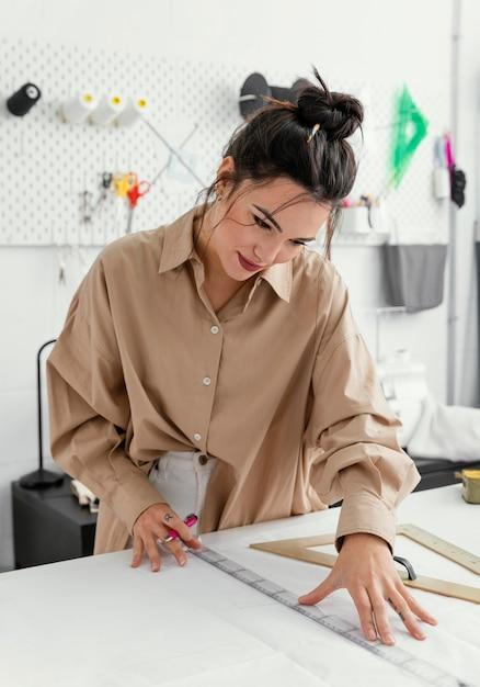 Fashion designer working in her workshop alone Free Photo
