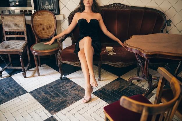 黒のベルベットのドレス、リッチでスタイリッシュな女性、エレガントなトレンド、長い細い脚、ハイヒールのサンダルの靴、靴を履いてヴィンテージカフェに座っているエレガントな美しい女性のファッションの詳細 無料写真