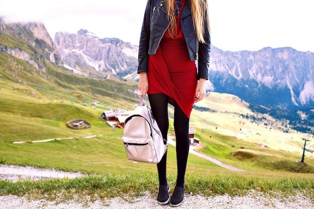 Dettagli di moda di donna turistica alla moda in posa mangiare giacca di pelle vestito elegante e zaino alla moda, vacanza di lusso alla moda nelle montagne di alp. Foto Gratuite