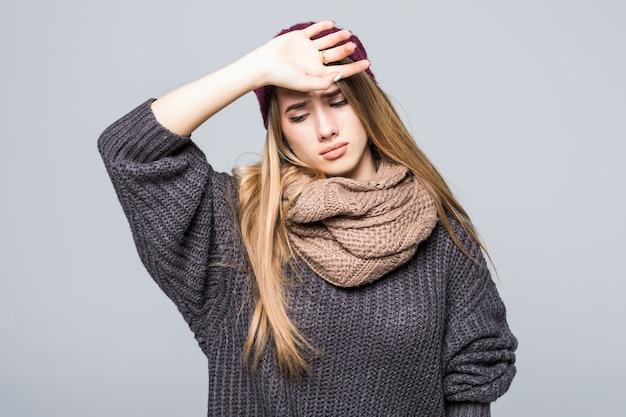 Модно одетая молодая модель имеет голову и боль в животе на сером Бесплатные Фотографии