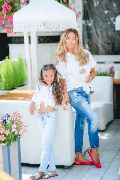 ファッション家族概念-スタイリッシュな母と子の摩耗。幸せな家族の肖像画:彼女の小さなかわいい娘を持つ若い美しい女性。若い娘は秋の市屋外で母親を抱擁します。 Premium写真