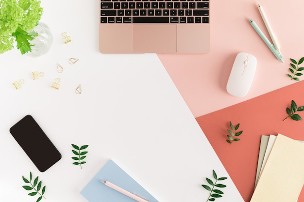 Fashion female office desk table with spring flowers and leaves, laptop, notebook, calculator, stationary, mobile phone and other office Premium Photo